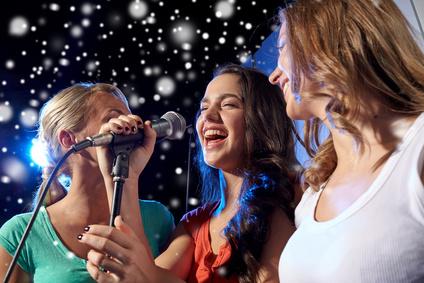 Karaoke Mikrofon - happy young women singing karaoke in night club